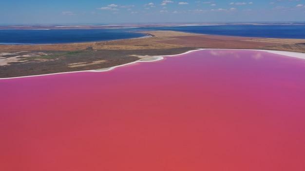 Фотография сверху вниз с воздушного дрона на естественном розовом озере куяльник в одессе, украина. озеро естественно розовеет из-за солей и мелких рачков артемии в воде. это чудо - редкость.