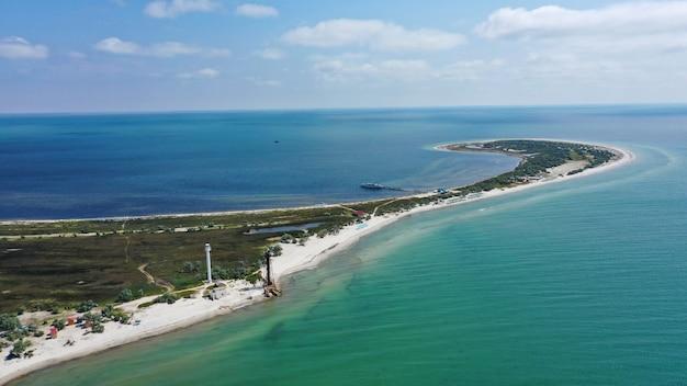 공중 무인 항공기는 모래 해변이 있는 섬의 바다 경치, 우크라이나의 청록색 맑은 흑해, 나무, 2개의 등대가 있는 사진을 하향식으로 촬영했습니다. 섬 dzharilgach.