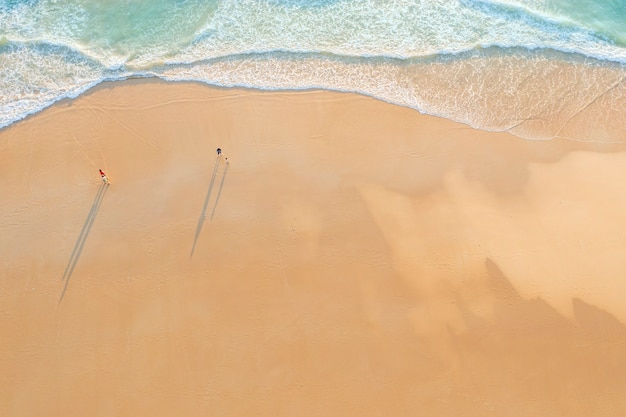 Aerial drone top view crowd of happy people relax at tropical beach with sunset in phuket, thailand, beautiful phuket beach is famous tourist destination at andaman sea. holiday summer concept