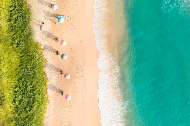 Aerial drone top view crowd of happy people relax at tropical beach with sunset in phuket thailand