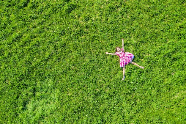 Aerial drone top view of happy smiling little girl in pink dress relaxing on green grass meadow during sunny summer day in park. free space.