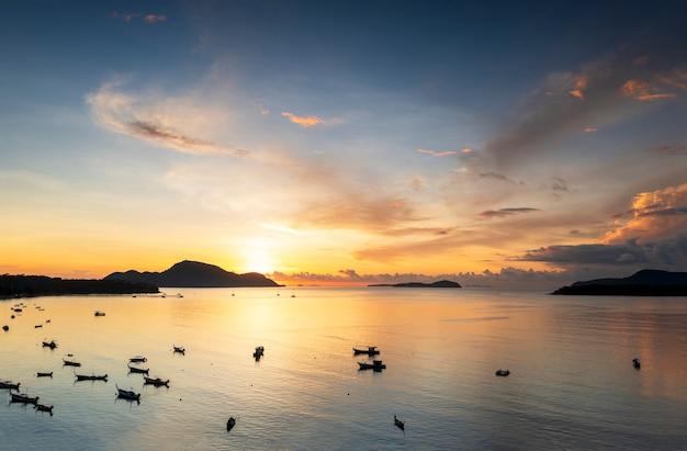 Воздушный дрон, вид сверху восхода солнца над тропическим пляжем с большим количеством длиннохвостых лодок