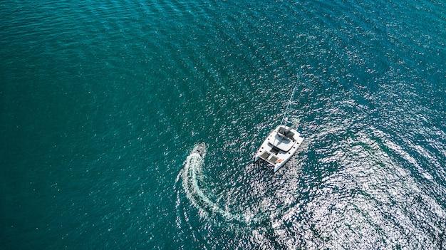 白いゴムボートと豪華ヨットの空中ドローントップビュー写真。 Premium写真