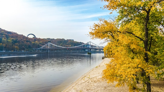 Aerial drone view of autumn pedestrian park bridge, yellow fall trees, truhaniv island, dnieper river and kyiv cityscape from above, city of kiev, ukraine