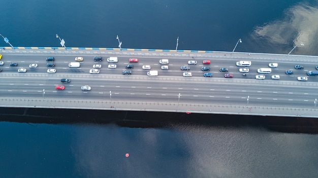 Aerial drone view of bridge road automobile traffic jam of many cars from above, city transportation concept