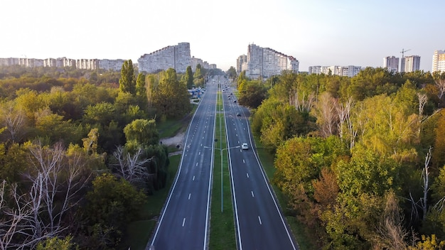 Aerial drone view of chisinau, moldova. road with cars and trees along it leading to the chisinau city gates, buildings