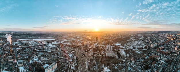 Aerial drone view of chisinau at sunrise. panorama view of multiple buildings, thermal station, roads, bare trees, snow.