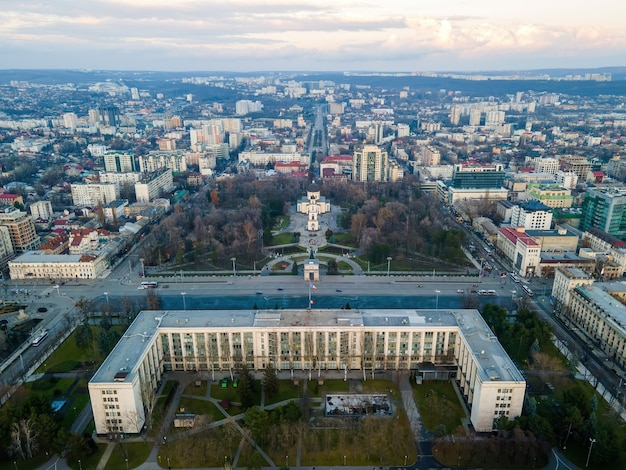 Aerial drone view of chisinau at sunset. panorama view of the city center with the government house and central park, multiple buildings, roads with moving cars, bare trees. moldova