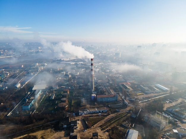 Aerial drone view of chisinau. thermal station with smoke coming out of the tube. buildings and roads. fog in the air. moldova
