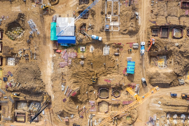 Aerial drone view of excavator loading the tipper truck at the construction site