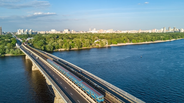 Aerial drone view of metro railway bridge with train and dnieper river from above, skyline of city of kyiv, kiev cityscape, ukraine