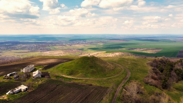 Aerial drone view of a mound with cross on the top in moldova. fields and villages in the distance