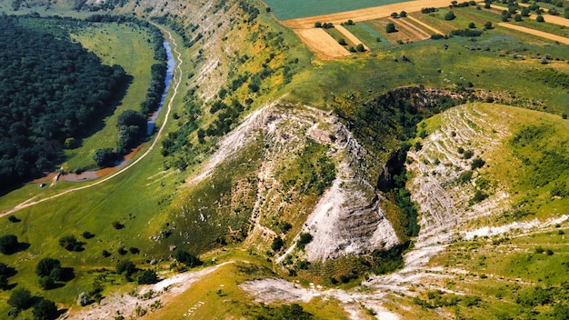 Aerial drone view of nature, green valley with river, rocky hill, moldova
