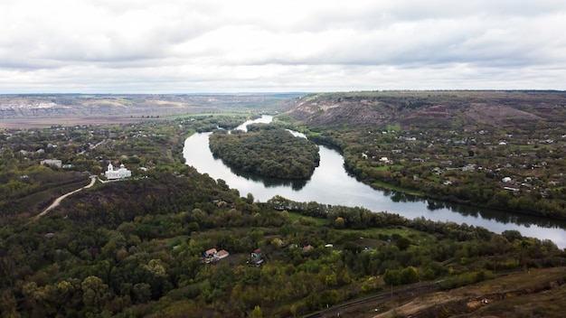 Aerial drone view of nature in moldova, floating river with reflecting cloudy sky and village near it, hills with trees