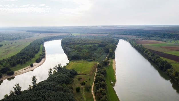 Aerial drone view of nature in moldova, floating river with reflecting sky, green fields with trees, fog in the air