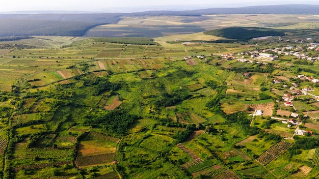 Aerial drone view of nature, village houses, green fields and hills, moldova