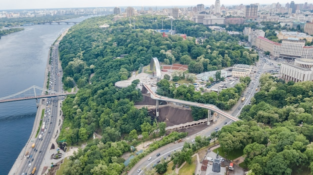 Aerial drone view of new pedestrian cycling park bridge construction, dnieper river, hills, parks and kyiv cityscape from above, city of kiev skyline, ukraine