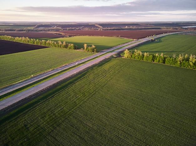 Воздушный беспилотный вид грузовиков, едущих по асфальтовой дороге вдоль зеленых полей в сельском пейзаже на закате.