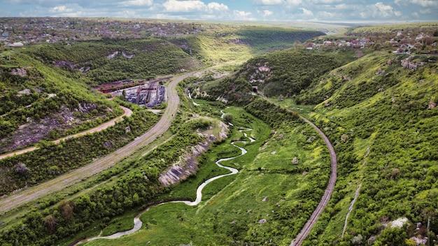 Вид с воздуха с дрона на долину с плавучей узкой рекой, две деревни у обоих склонов железных дорог