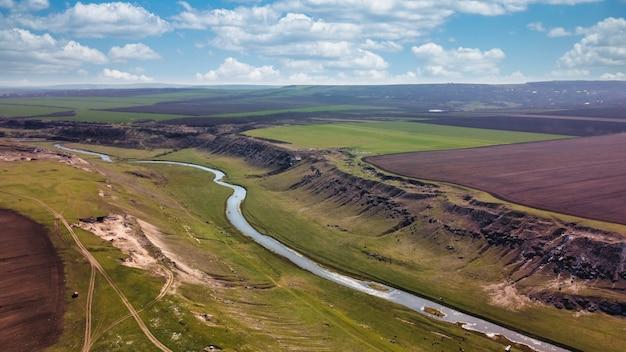 Вид с воздуха с дрона на долину с плавающей рекой, поля вокруг в молдове