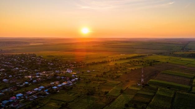Вид с воздуха с беспилотника на деревню в молдове на закате. широкие поля вокруг него