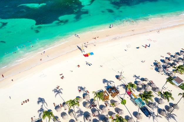 짚 우산, 야자수, 보트가 있는 아름다운 카리브해 열대 해변의 공중 무인 항공기 보기. 바바로, 푼타 카나, 도미니카 공화국. 휴가 배경.