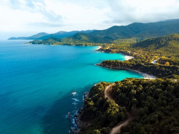 ギリシャのハルキディキの青い海と風の強い山道の空中ドローンビュー