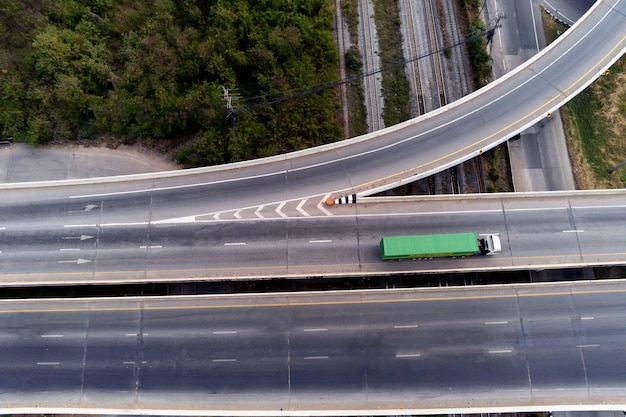아스팔트 고속도로에서 녹색 컨테이너, 운송 개념, 수입, 수출 물류 산업 운송 육상 운송이 있는 고속도로에서 화물 흰색 트럭의 공중 무인 항공기 보기