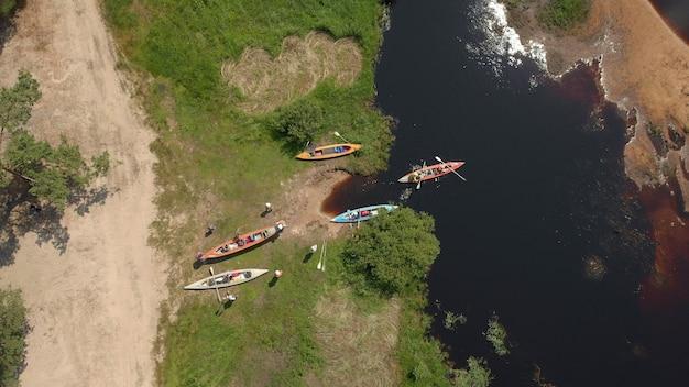川のグループカヤックの空中ドローンビュー。ラフティング。カヤックとカヌーの観光拠点、夏のアドベンチャーカヤック、カヌーへのラフティング。カヤックの上面図