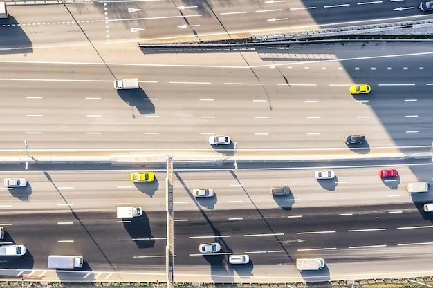 화창한 날 현대 도시에서 바쁜 도시 교통이 있는 고속도로의 공중 무인 항공기 보기.
