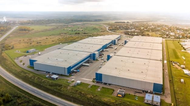 Вид с воздуха на большие современные промышленные складские здания. логистические перевозки грузовой терминал с высоты птичьего полета.