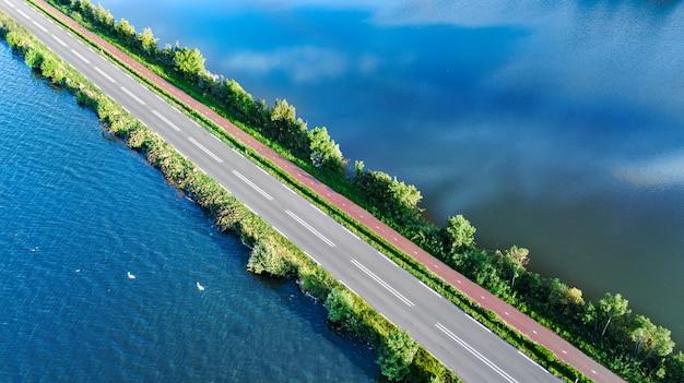 干拓地のダム、上から、北オランダ、オランダからの車の交通の高速道路とサイクリングパスの空中ドローンビュー