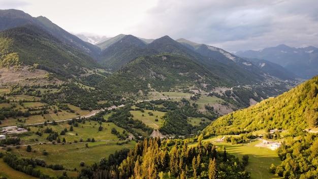 日没の谷の山と丘の斜面でのジョージア州の自然の空中ドローンビュー