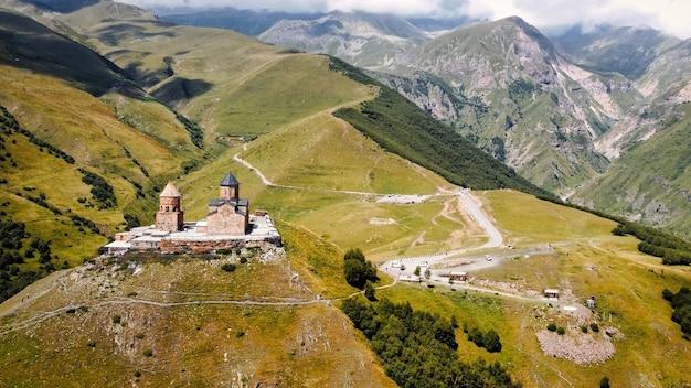 ジョージアコーカサス山脈ゲルゲティ三位一体教会の自然の空中ドローンビュー