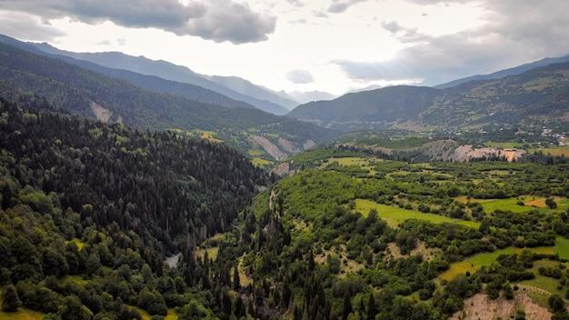 緑に覆われたジョージアバレーの山々と丘の斜面の自然の空中ドローンビュー