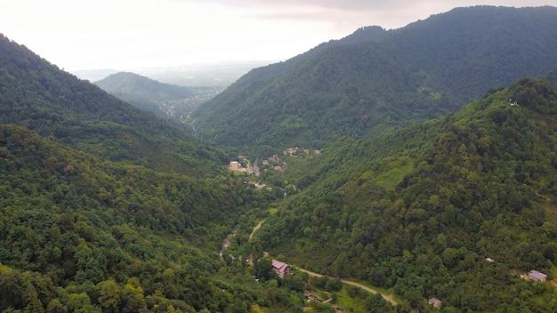 狭い川と村の丘の斜面があるジョージアバレーの自然の空中ドローンビュー