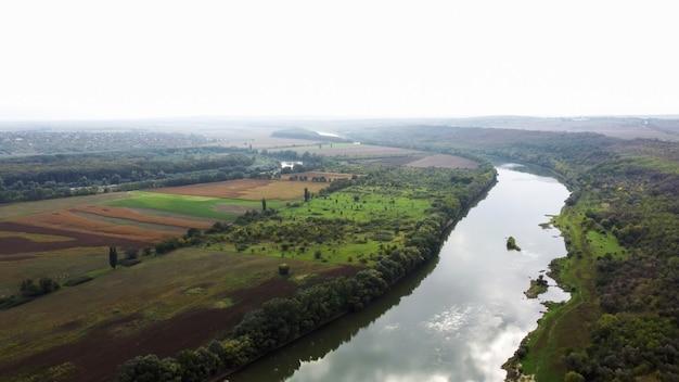 몰도바에서 자연의 공중 무인 항공기보기, 하늘을 반영하는 강, 나무가있는 녹색 들판, 공중에 안개