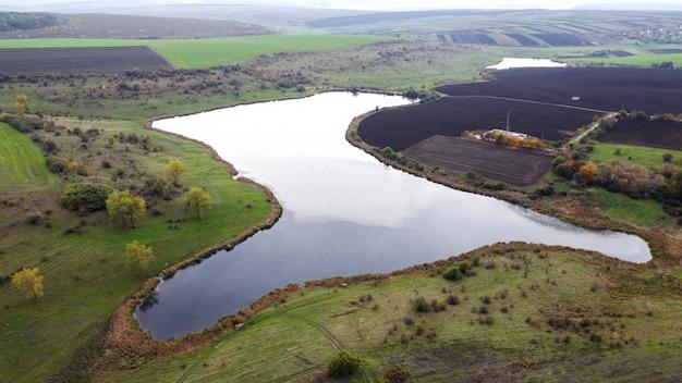 モルドバの自然の空中ドローンビュー、曇り空が反射する湖、播種されたフィールド、木