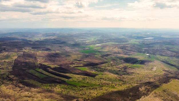 Вид с воздуха на природу молдовы с беспилотника. низкие холмы с голыми деревьями и кустарниками, поля