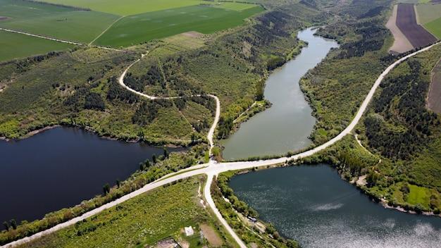モルドバの道路の自然の空中ドローンビューは、橋の低い丘と野原のある川に浮かんでいます