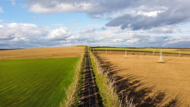 Вид с воздуха на природу молдовы, засеянные поля, дорогу с движущейся машиной, деревья вдоль нее, облачное небо
