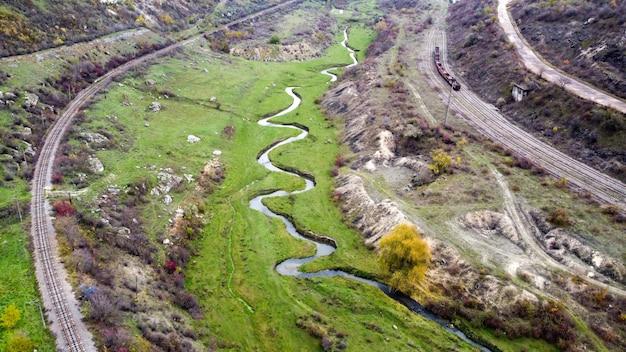 モルドバの自然の空中ドローンビュー、渓谷に流れ込む小川、まばらな植生と岩のある斜面、動く列車、曇り空