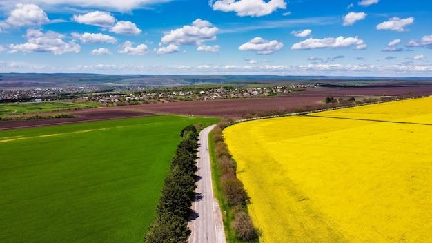 Вид с воздуха на природу молдовы с беспилотника. желто-зеленые поля, деревня вдалеке