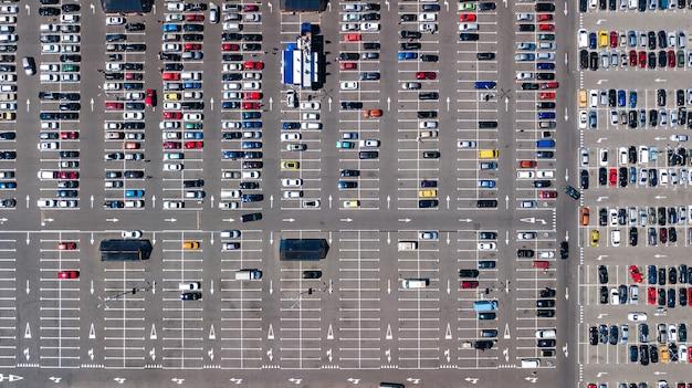Воздушный беспилотный вид на стоянку с множеством автомобилей возле торгового центра сверху, городской транспорт и городская концепция