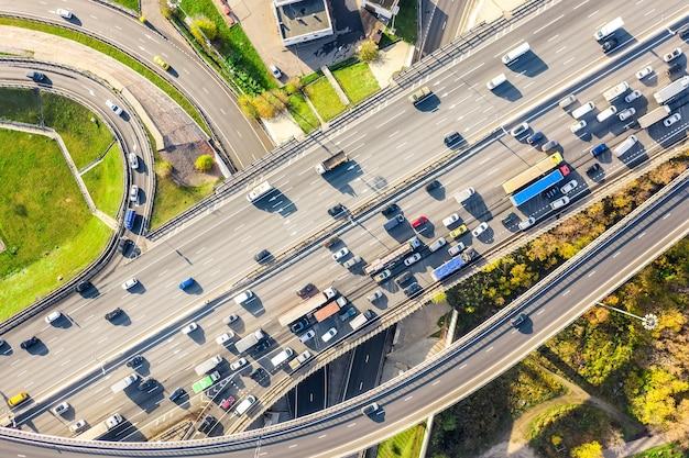 화창한 날 현대 도시의 바쁜 도시 교통과 도로 교차로 또는 고속도로 교차로의 공중 무인 항공기 보기. 교통 체증 조감도.