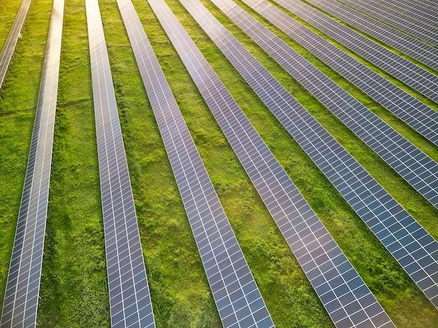 Воздушный беспилотный вид солнечной электростанции на зеленом лугу в солнечный день