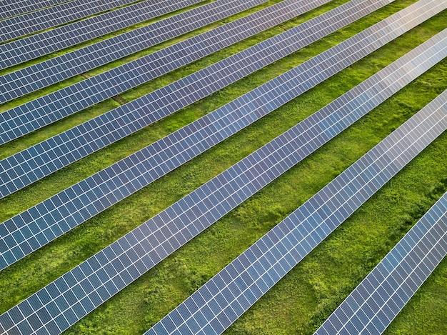 晴れた日の緑の牧草地の太陽光発電所の空中ドローンビュー