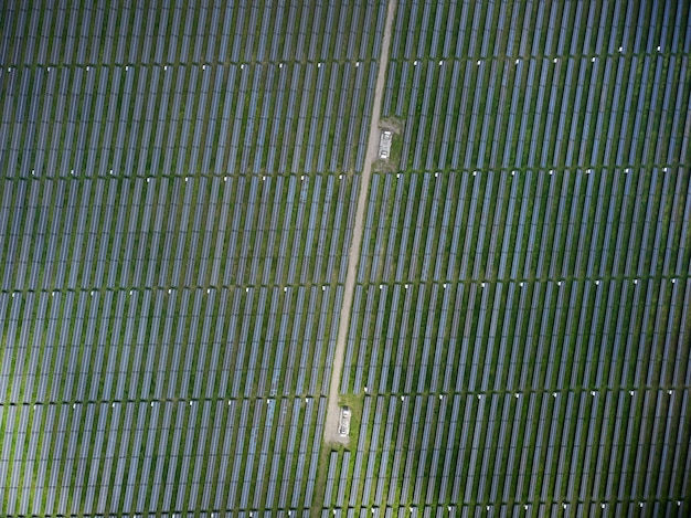 Воздушный беспилотный вид солнечной электростанции на зеленом лугу в солнечный день.