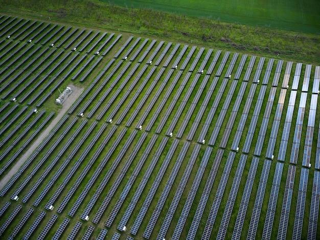 화창한 날 푸른 초원에 있는 태양광 발전소의 공중 무인 항공기 보기.