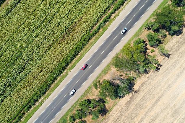 벗겨진 해바라기 밭과 말린 빈 필드의 공중 무인 항공기보기는 나무와 고속도로로 나뉩니다.